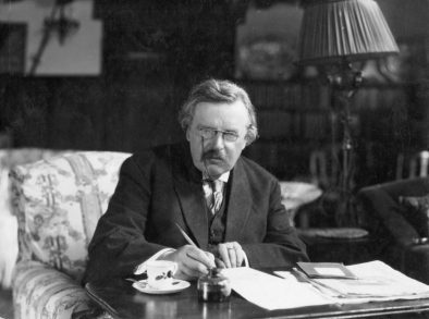 Portrait photograph of G.K. Chesterton sitting at desk.