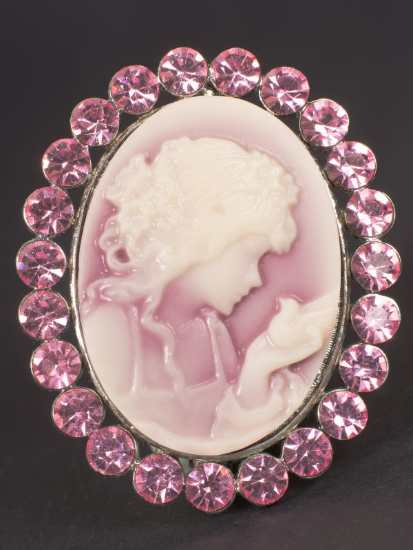 Photograph of cameo of girl holding out hand surrounded by pink gems.