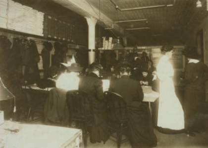 Women factory workers sitting at table.