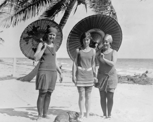 Photograph of three women on a beach holding parasols, 1915.
