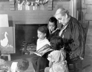 Photograph of Jane Addams reading to children at Hull House.