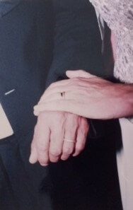 Close-up of bride and groom's hands.