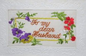 Embroidered postcard reading For my dear husband, with flowers.