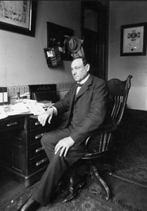 Photograph of Harvey Wiley sitting at desk, ca. 1900.
