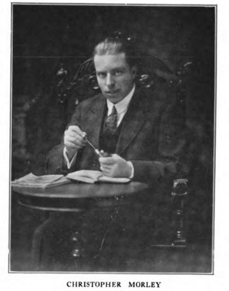 Portrait photograph of Christopher Morley sitting at a table, ca. 1918.