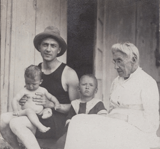 Photograph of William Carlos Williams, wearing fedora, with mother and sons, ca. 1918.
