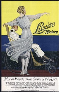 1919 ad for Luxite hosiery. Woman with dress blowing, showing hose, standing with man in wheelchair.