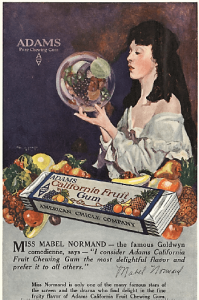 1919 California fruit gum ad, woman holding globe with fruit inside.