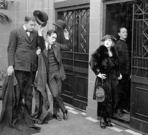 Men tipping hats at woman going into elevator, from the John Lloyd film High and Dizzy, 1920.