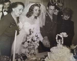 Rita Senger Stein with her son and daughter-in-law, cutting cake, at their wedding.